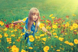 girl playing in flowers