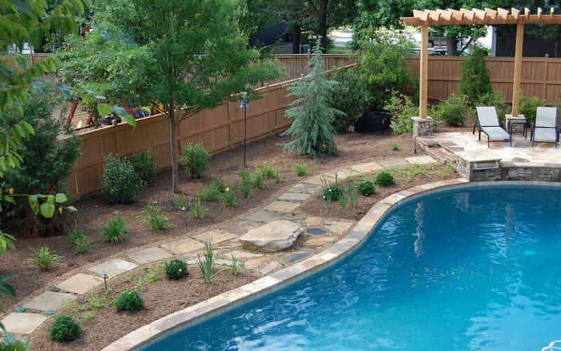High-end Atlanta pool renovation with stone hardscaping and custom pergola lounge area