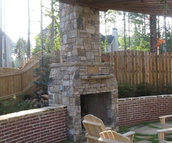 Custom fireplace with pergola and brick half wall