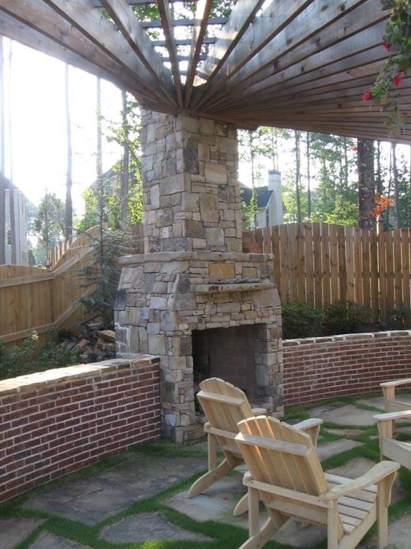 Custom fireplace with pergola and brick half wall