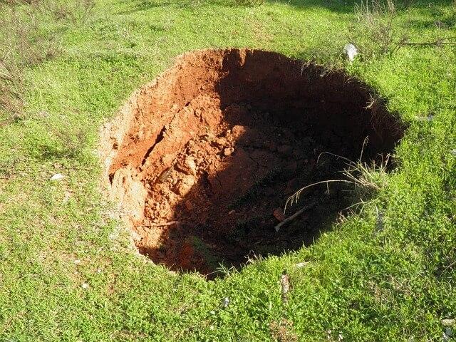 Sinkhole in grassy lawn