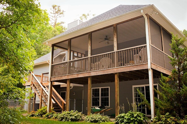 Back of large home with second story screened-in porch