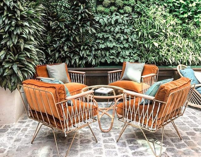 Patio with plush seating area surrounded by greenery